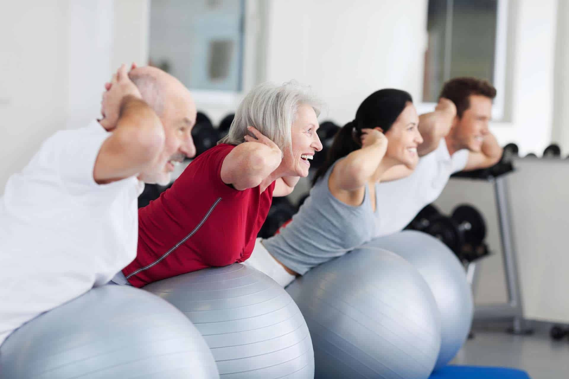 People of all ages exercising on Swiss Balls in a Pilates session